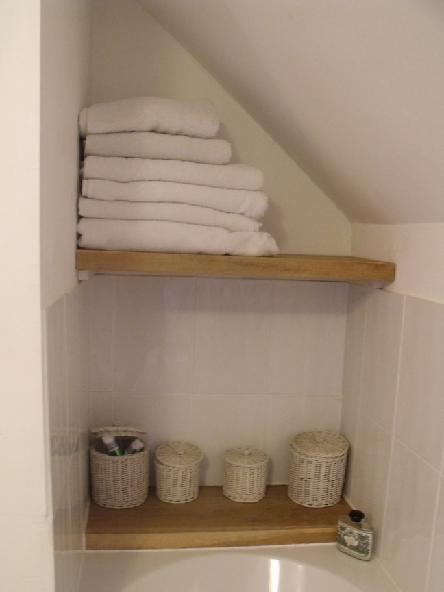 oak shelving above a bath